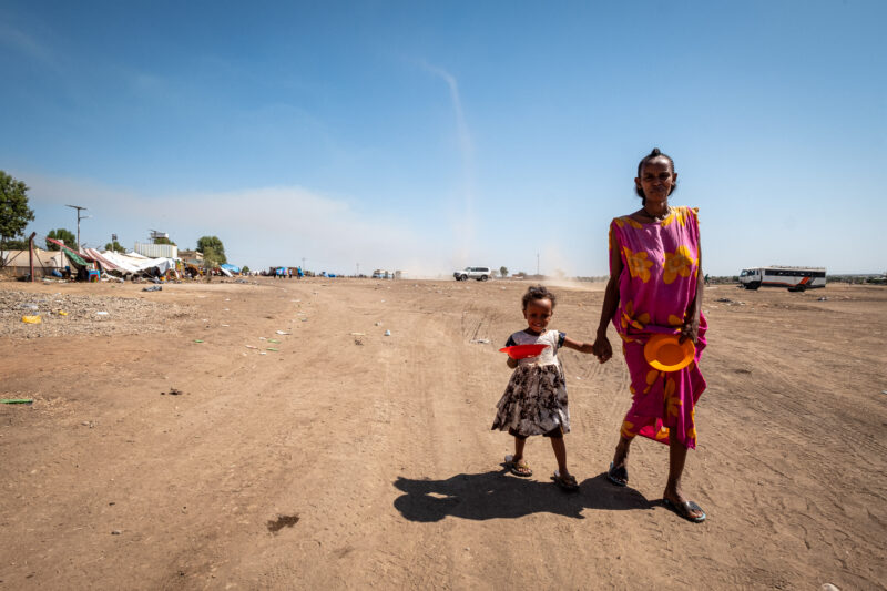 A mother and daughter walk along a dirt path, Ethiopian refugees in Sudan, photo by Joost Bastmeijer