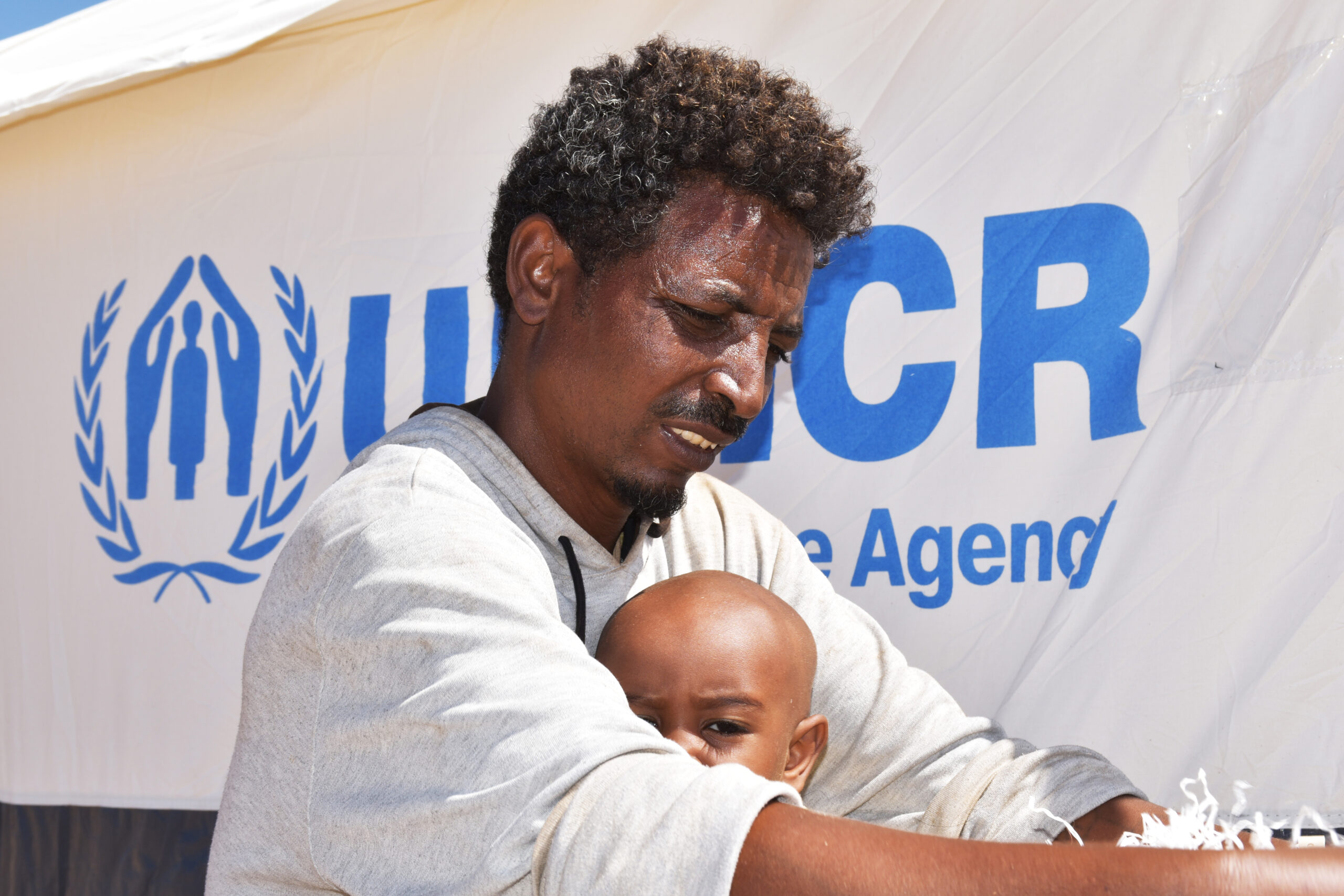 An Ethiopian man holding his son sitting outside
