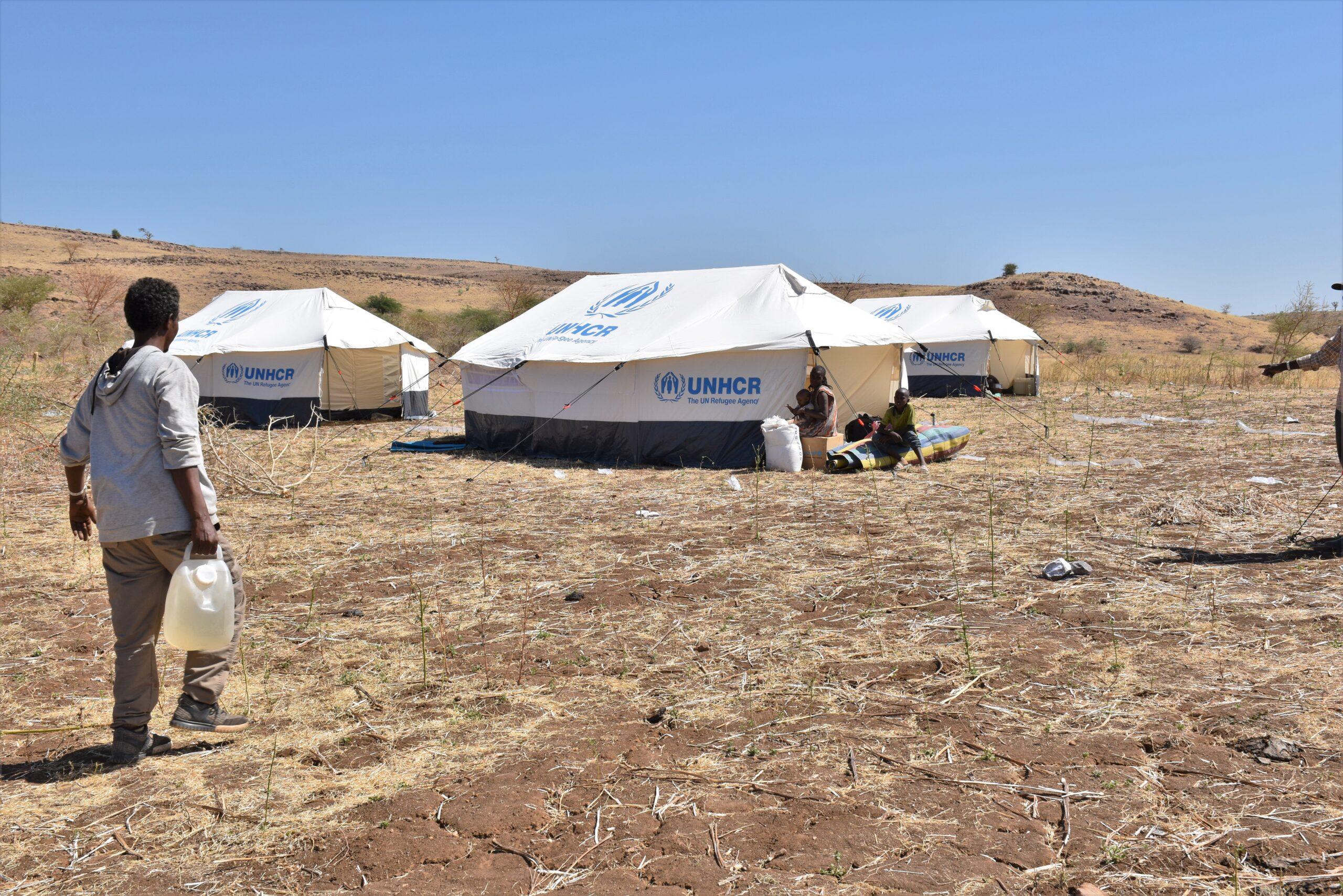 Burhani carries water to his tent in Um Rakouba