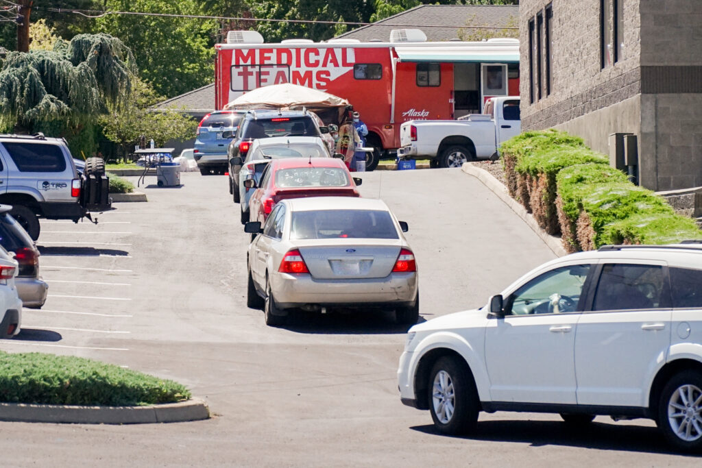 A line of cars wait in front of a Medical Teams mobile testing center