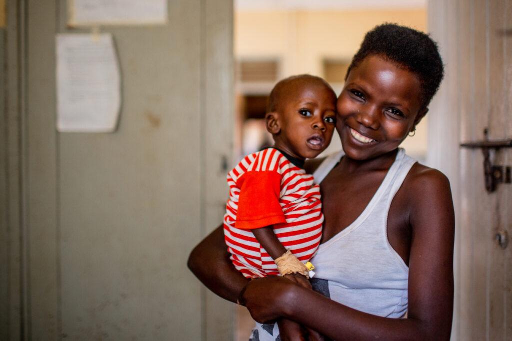 Tusingirwe holds her baby, Namara, in a medical clinic in Uganda.