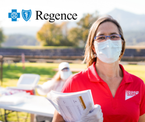 A woman wearing a bright red polo shirt and face masks holds paperwork and stands outside of an outdoor COVID-19 testing clinic in Cascade Locks, Oregon.