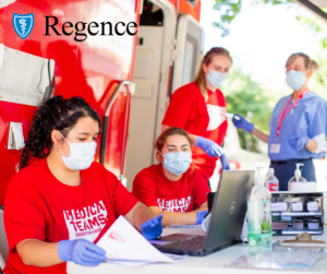 A group of women, wearing red shirts and face masks, gather around a table outside of a red mobile medical van and look at a laptop screen.