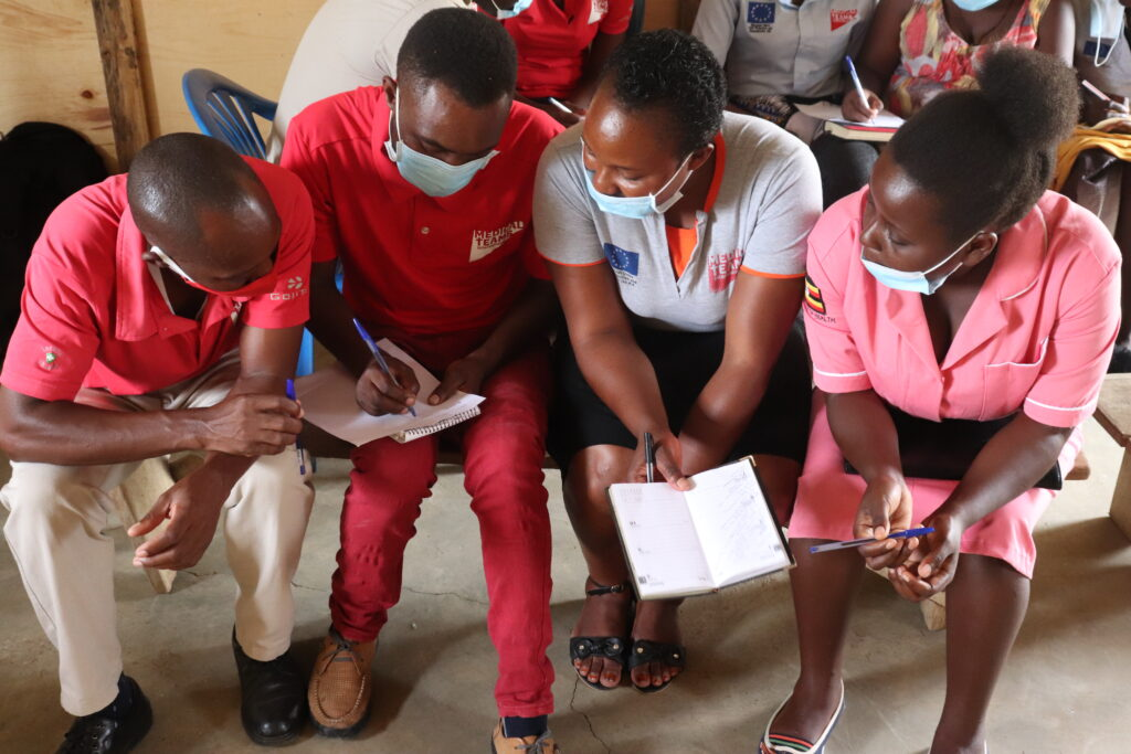 Four staff members compare notes at a training in Uganda